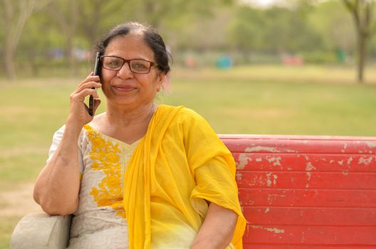 Senior Indian woman speaking on her smart phone, sitting on a red bench in a park in New Delhi. Concept shot showcasing technology adoption by senior citizens. Digital India