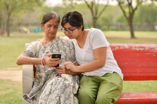 Young Indian girl with an old Indian Bengali woman looking at the mobile phone and busy talking sitting on a red bench in a park in New Delhi, India