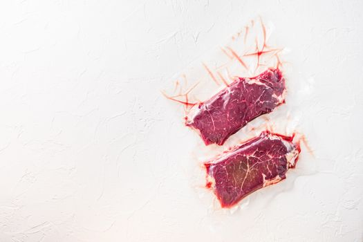 Set of vacuum packed organic beef meat rump steak on white concrete textured background, top view space for text.