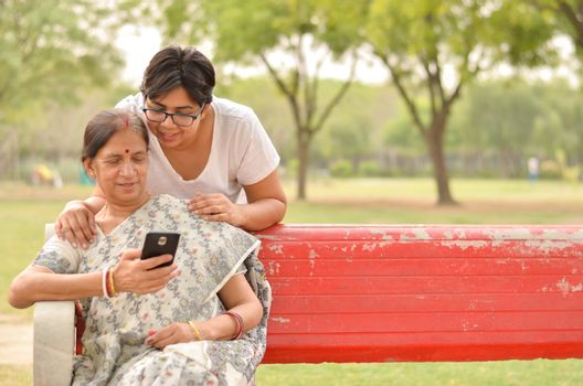 Young Indian girl keeping her hands on her old Indian Bengali mother's shoulders looking at the mobile phone and busy talking sitting on a red bench in a park in New Delhi, India. Concept Mother's day
