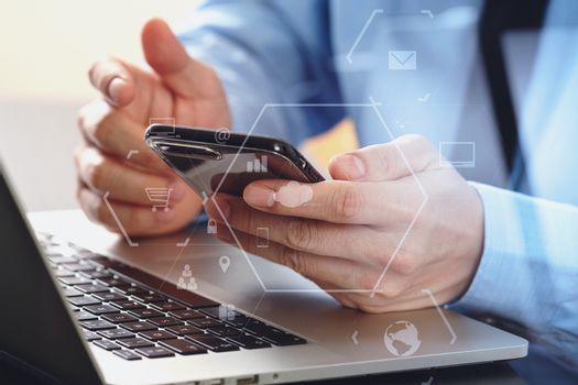 close up of businessman working with mobile phone and laptop com