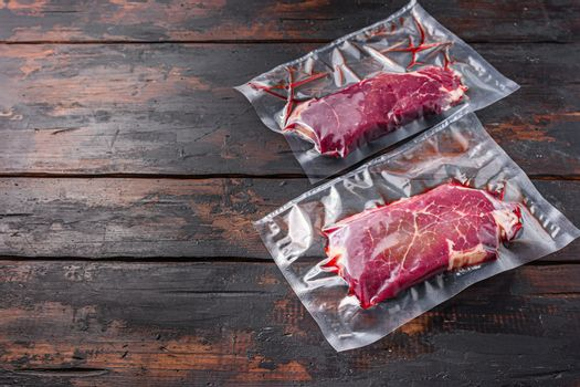 Vacuum packed Rump Steak from organic beef on dark old wooden background, side view with space for text.
