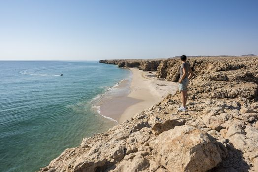 Woman admiring wild beach, coast of Ras Al Jinz, Sultanate of Oman