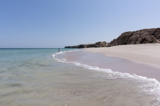Woman alone at a wild Beach of Ras Al Jinz and going to swim in the ocean (Gulf of Oman), Oman, Sultanate of Oman. It is close to Ras Al Hadd and many turtles are coming in the region to nest