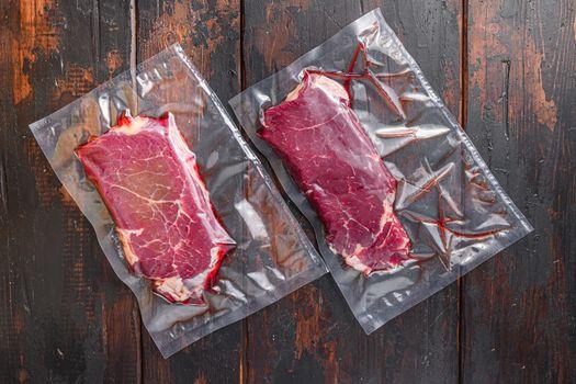 Vacuum packed Rump Steak from organic beef on dark old wooden table, top view.