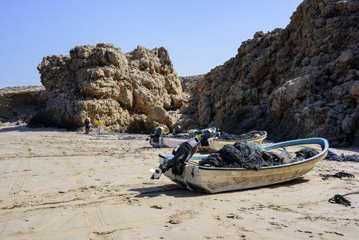 Fishermen arranging their net on the beach of Ras Al Jinz besides some boats, Oman
