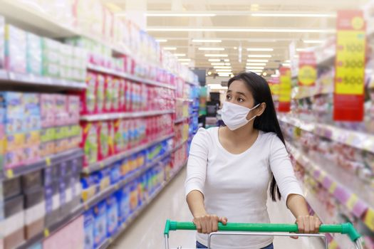 Asian woman wear face mask push shopping cart in supermarket. Girl looking grocery to buy  something. During coronavirus crisis or covid19 outbreak. Women wearing protective face mask new normal concept.