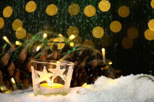 christmas theme with candles, snow, pine cone and christmas light with pokeh effect