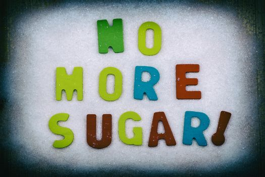 """""""NO MORE SUGAR!"""" Colorful text and letters in wood on white sugar crystals background and black border"""