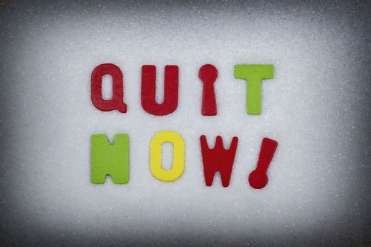 """""""Quit now!"""" Colorful text and letters in wood on white sugar crystals background and black vignette border"""