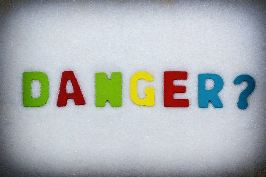 """""""Danger?"""" Colorful text and letters in wood on white sugar crystals background and black vignette border"""