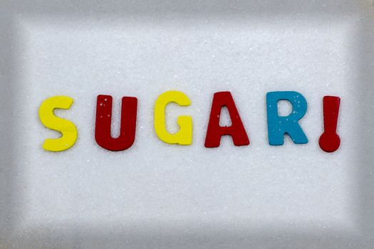 """""""SUGAR!"""" Colorful text and letters in wood on white sugar crystals background and light black frame"""