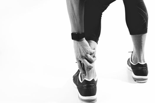 Runner sportsman holding ankle in pain with Broken twisted joint running sport injury and Athletic man touching foot due to sprain,black and white