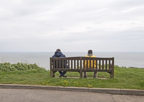 Two people sat on bench with sea view