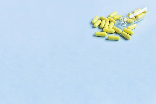 Yellow capsules are poured out of a bottle on a blue background. Omega-3 vitamins. food Supplement. Fish oil in capsules. Free space. space for text. copy space. blurred background. Selective focus.