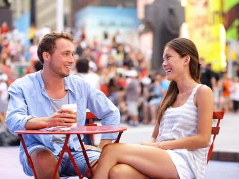 Dating couple, New York, Manhattan, Times Square dating drinking coffee smiling happy sitting at red tables enjoying their tourism vacation travel in the USA. Asian woman, Caucasian man.