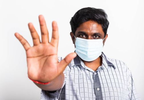 Closeup Asian handsome black man wearing surgical hygienic protective cloth face mask against coronavirus and raising hand stop sign, studio shot isolated white background, COVID-19 medical concept