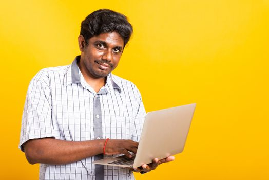 Asian happy portrait young black man smiling standing wear shirt holding and typing laptop computer he looking to camera isolated, studio shot yellow background with copy space
