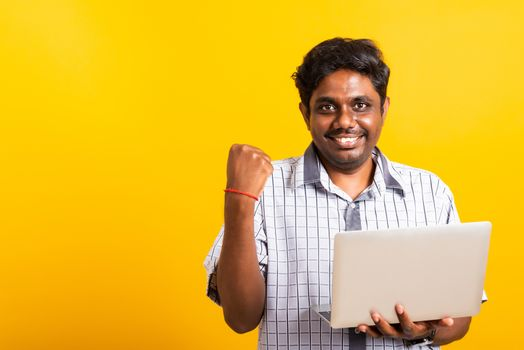 Closeup Asian happy portrait young black man excited holding laptop computer clenching fists and raising a hand for winner sign celebrating his success, studio shot isolated on yellow background