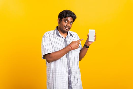 Asian happy portrait young black man smile standing wear shirt making finger pointing on smart digital mobile phone blank screen isolated, studio shot yellow background with copy space