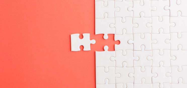 Top view flat lay of paper plain white jigsaw puzzle game texture last pieces for solve and place, studio shot on a red background, quiz calculation concept