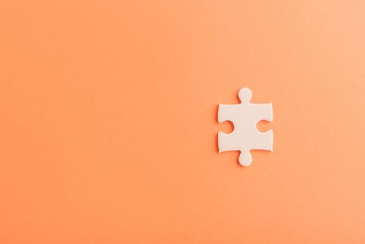 Top view flat lay of one paper plain white jigsaw puzzle game last pieces for solve, studio shot on an orange background, quiz calculation concept