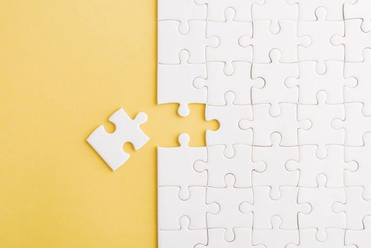Top view flat lay of paper plain white jigsaw puzzle game texture last pieces for solve and place, studio shot on a yellow background, quiz calculation concept