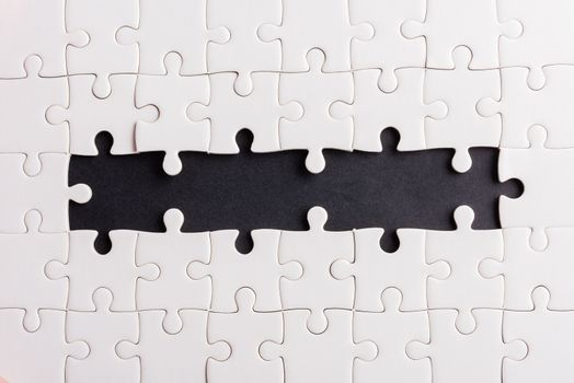 Top view flat lay of paper plain white jigsaw puzzle game texture incomplete or missing piece, studio shot on a black background, quiz calculation concept