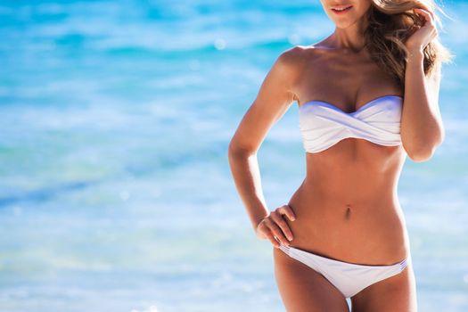 Woman with perfect body in white bikini posing on sea background