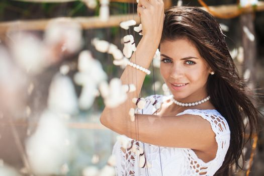 Beautiful woman in white dress on vacation posing with garland of shells and corals