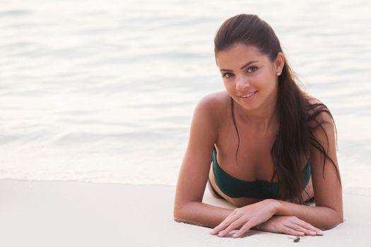 Smiling beautiful woman in bikini lying on beach at sunset time