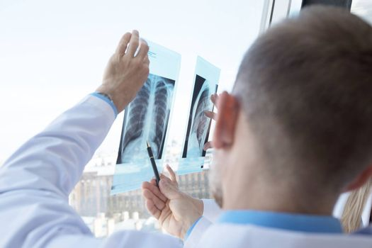 Two doctors examining a x-ray film by the window at clinical office