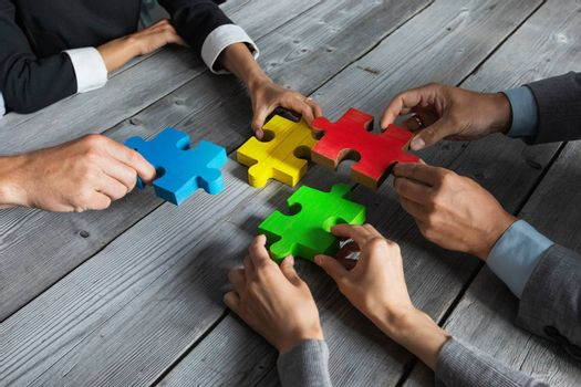 Business people team sitting around meeting table and assembling color jigsaw puzzle pieces unity cooperation ideas concept