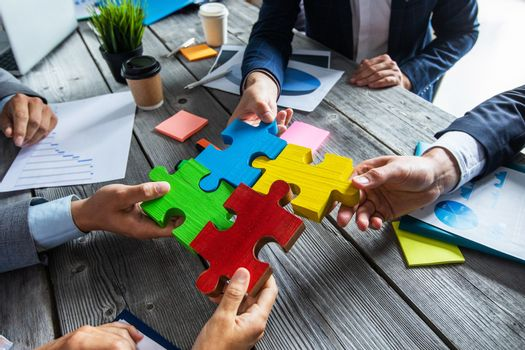 Business people team sitting around meeting table and assembling color jigsaw puzzle pieces over financial data reports