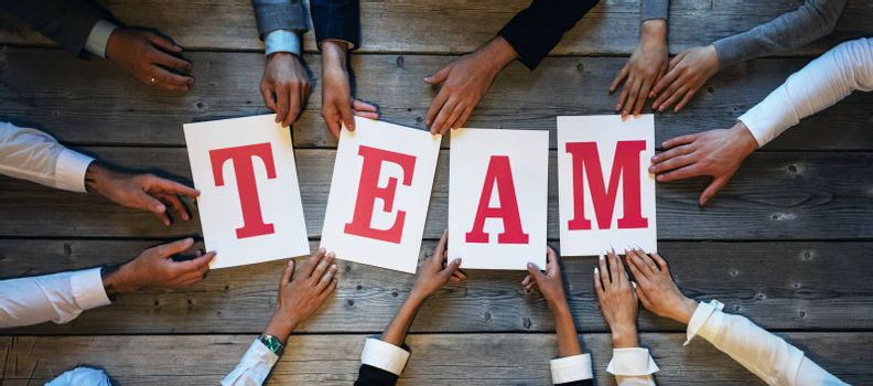 Business people holding TEAM letters printed on paper
