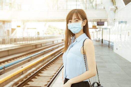 business woman wearing face mask at train station