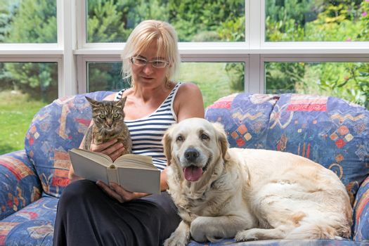 Blond middle aged woman is sitting on a couch and reading a book. Striped cat and Golden Retriever dog are sitting with her together. The pets are looking at the camera.