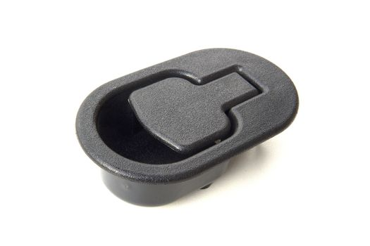 Black plastic object on a computer table used for strapping wires and cords together.