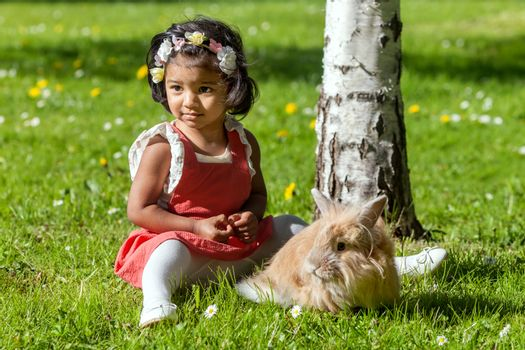 A two years old Asian girl with rabbit is playing in park