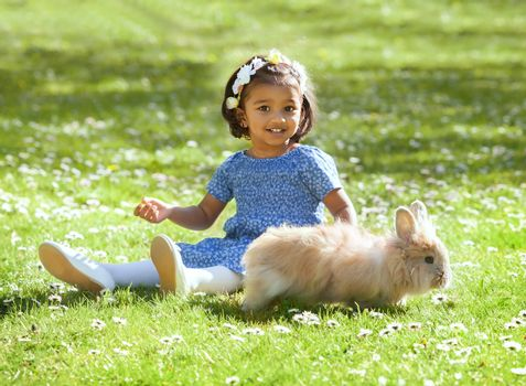 A small Asian girl  with home rabbit on green grass