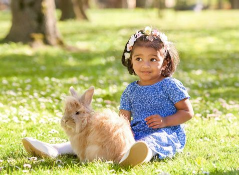 A small  girl is sitting with rabbit on green grass in spring park