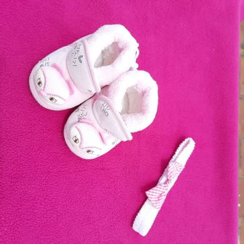 Baby shoes placed beautifully in pink background with bow band