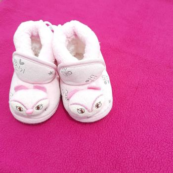 Baby shoes placed beautifully in pink background