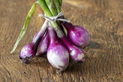 bunch of purple onions on wood