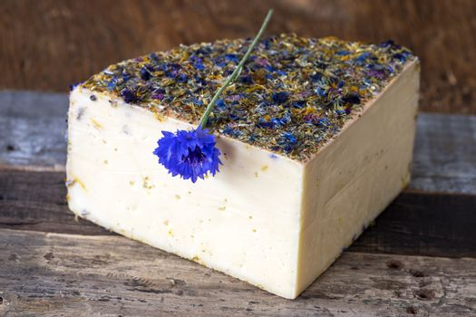 mountain cheese with flowers on wood