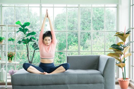 Attractive and healthy woman Asian are exercising Stretching with yoga postures at home helps to balance life.copy space is on the left side of the image For adding text