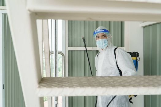 Workers wear protective clothing and wear a mask. Spraying disinfectants for cleaning inside the building. Cleaning service professionals are becoming popular After the spread of coronavirus