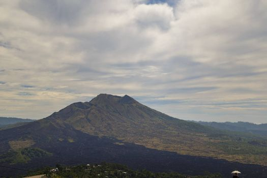 View of Indonesia Batur active vulcano with black lava all around.