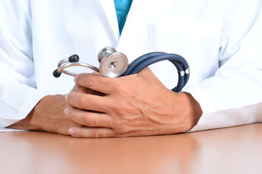 Closeup of a doctors hands holding a stethoscope on top of his desk.