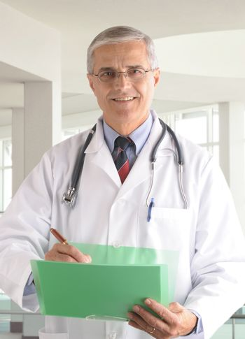 Middle aged doctor writing in chart in modern medical facility